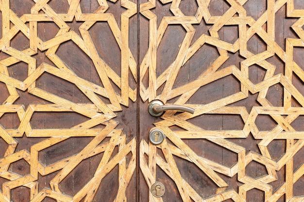 Fragment starych drewnianych drzwi z dekoracyjnym wzorem architektonicznym teksturowanym tłem
