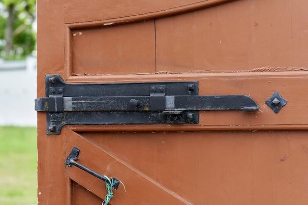 Fragment starych drzwi fortecznych z kutymi metalowymi ryglami i zamkami