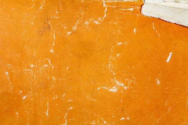 Fragment tekstury starego papieru pomarańczowego z zadrapaniami i uszkodzeniami. abstrakcyjne tło