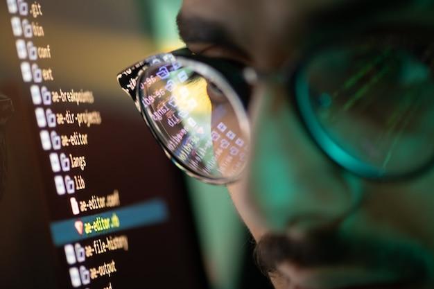 Fragment twarzy młodego współczesnego programisty w okularach z odbiciem ekranu z odkodowaną informacją na soczewce