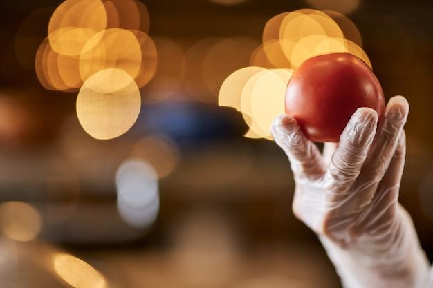 Fragment zdjęcia dojrzałego pomidora w dłoni szefa kuchni