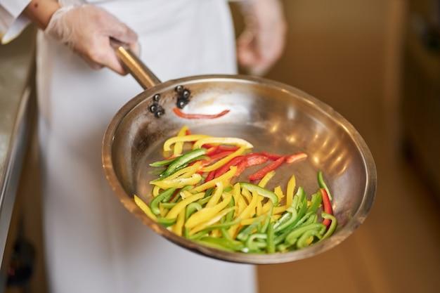 Fragment zdjęcia kucharza z patelnią pełną pokrojonej papryki