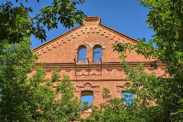 Fragment zrujnowanego muru z dachem z czerwonej cegły otoczony zielenią