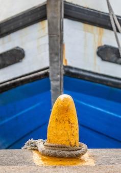Fragmenty dziobu łodzi rybackich przywiązanych linami do pomostu.