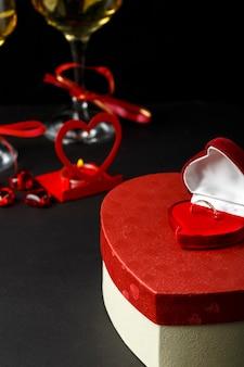 Fragmenty kieliszki z szampanem przewiązane czerwoną wstążką na czarnym tle pudełka w kształcie serca z prezentem i pierścieniową częścią wizerunku. zdjęcie pionowe