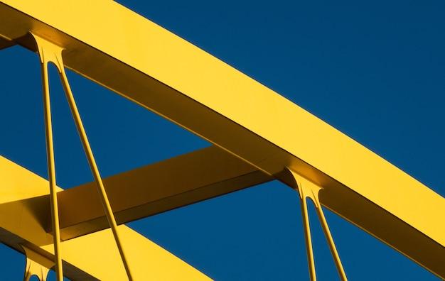 Fragmenty nowoczesnej konstrukcji żółtej na niebieskim tle