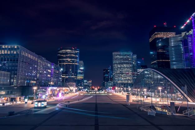 Francja. dzielnica nocna la défense w paryżu. duży plac dla pieszych otoczony nowoczesnymi wieżowcami