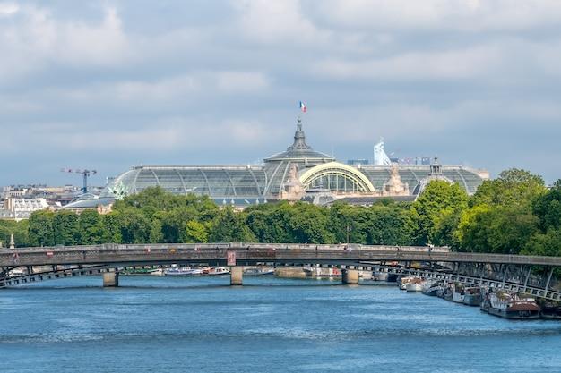 Francja. letni dzień w paryżu. dach wielkiego pałacu i barki mieszkalne zacumowane są przy nabrzeżu sekwany