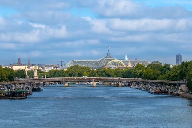 Francja. letni dzień w paryżu. zachmurzone niebo nad sekwaną. szklany dach wielkiego pałacu