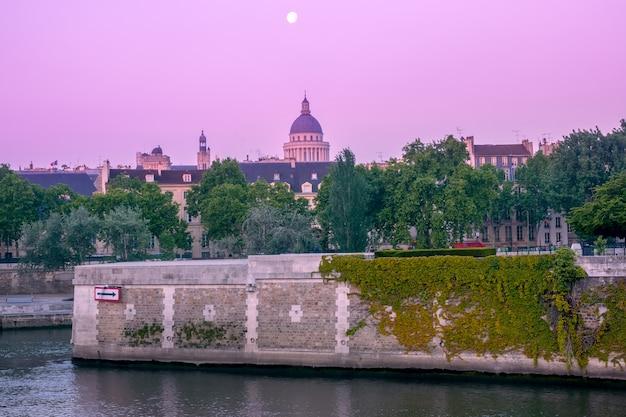 Francja. letni paryż. wczesny różowy poranek nad brzegiem sekwany. nasypy granitowe