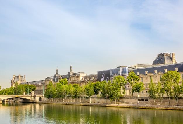 Francja. letni słoneczny dzień w paryżu. nabrzeże sekwany i fasada luwru