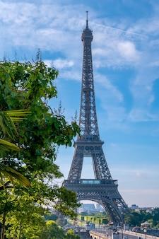 Francja. letni słoneczny poranek w paryżu. wieża eiffla i zielone drzewa