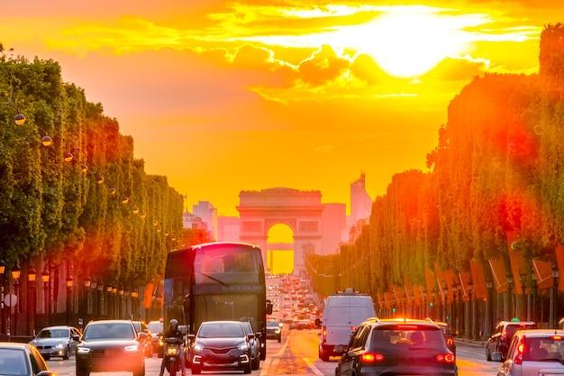 Francja. letni złoty zachód słońca na polach elizejskich w paryżu. łuk triumfalny i ruch samochodowy