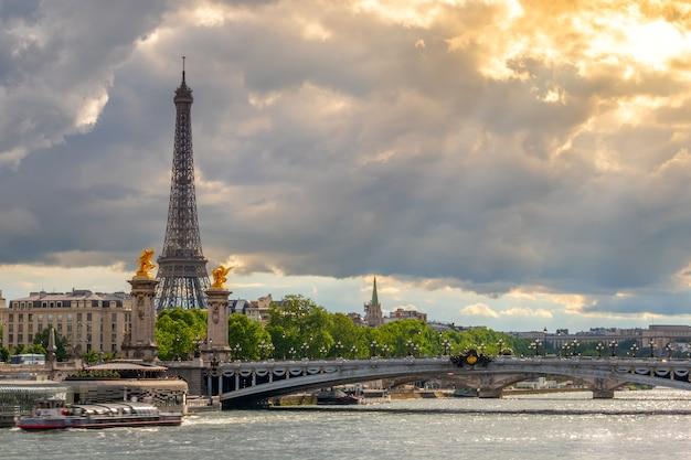 Francja. paryż. ciężkie chmury i promienie słońca. ruch na sekwanie