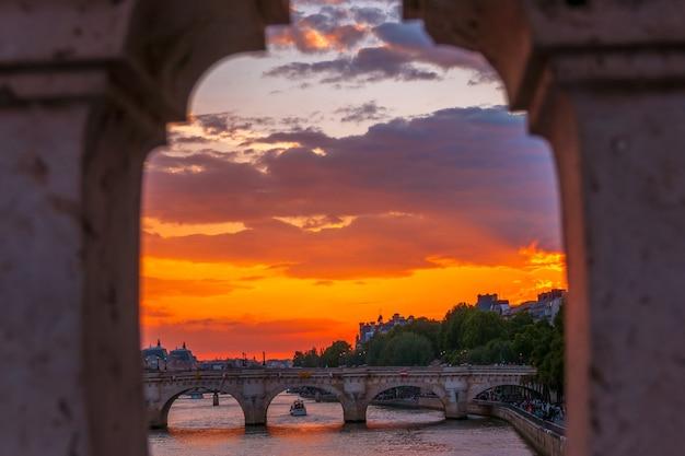 Francja. paryż. kolorowy zachód słońca nad sekwaną. widok przez kratownicę mostu