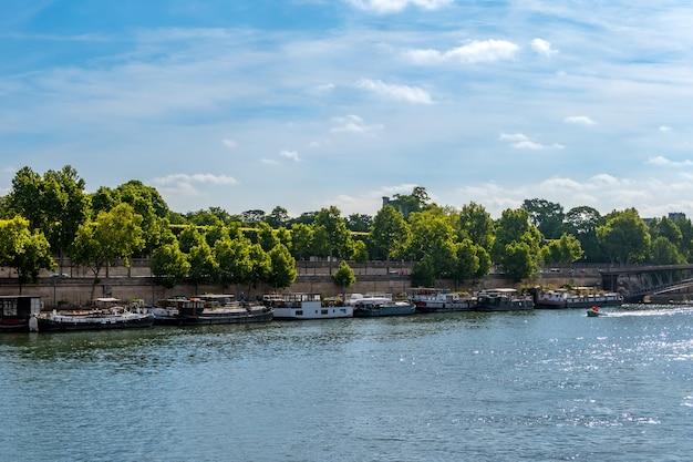 Francja. paryż. letni dzień. sekwana. wiele domów na wodzie zacumowanych przy granitowych skarpach