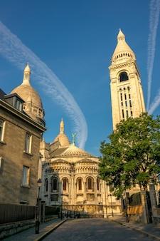 Francja. paryż. montmartre. pusta ulica i dzwonnica bazyliki najświętszego serca pana jezusa. letni słoneczny dzień i dziwaczne chmury na niebieskim niebie