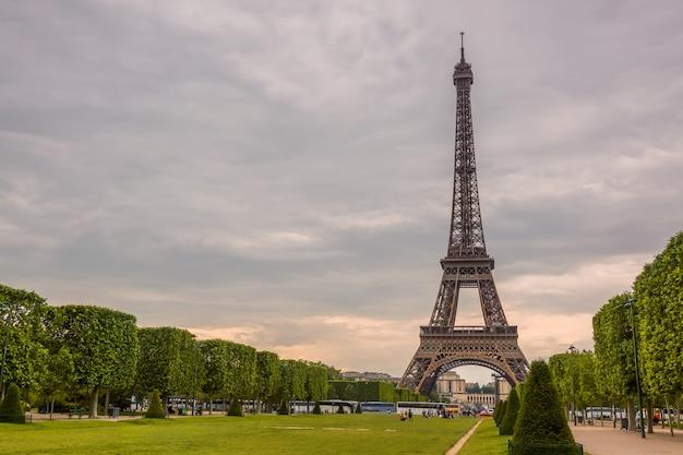 Francja. paryż. pochmurny letni dzień. champ de mars i wieża eiffla. wielu turystów i autobusów