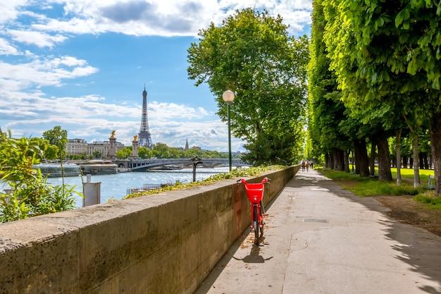 Francja. paryż. słoneczny dzień. nabrzeże sekwany z widokiem na wieżę eiffla. jasnoczerwony rower
