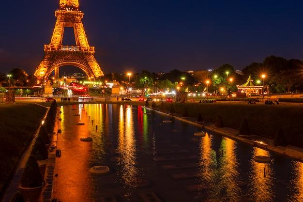 Francja, paryż. turyści i samochody w pobliżu wieży eiffla z oświetleniem nocnym. refleksje w niepełnosprawnych fontannie ogrodów trocadero