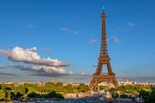Francja. paryż. wieża eiffla w zachodzie słońca promienie słońca. niska chmura na niebieskim niebie