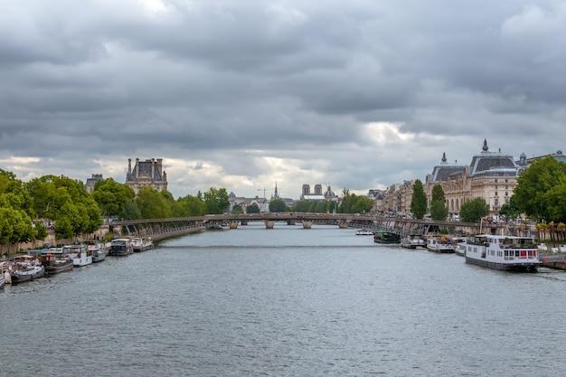 Francja. pochmurny letni dzień nad sekwaną. wiele barek mieszkalnych zacumowanych przy granitowych skarpach