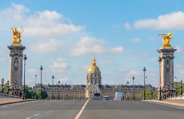Francja. słoneczny letni dzień w paryżu i fasada esplanade invalides. samochody i ludzie na moście aleksandra iii