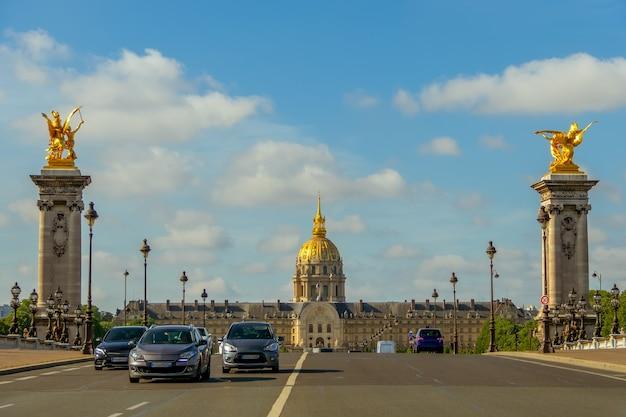 Francja. słoneczny letni dzień w paryżu. samochody na moście aleksandra iii i fasadzie esplanade invalides