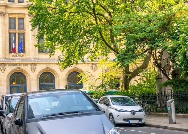 Francja. słoneczny letni dzień w paryżu. zielony ogród w pobliżu uniwersytetu sorbony. na wąskiej uliczce zaparkowanych jest kilka samochodów. samochód elektryczny podłączony do ładowarki