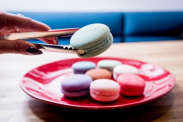 Francuscy kolorowi macarons na czerwonym talerzu. restauracja.