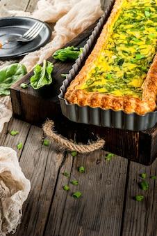 Francuska domowa kuchnia. zapiekanka. ciasto. quiche lorraine z ciasta francuskiego, z młodą zieloną cebulą i szpinakiem. na starym drewnianym stole w stylu rustykalnym. ciąć. w formie do pieczenia. talerz, widelec, nóż.