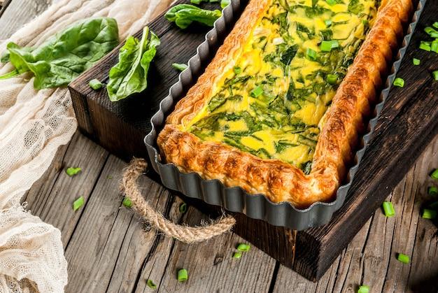 Francuska domowa kuchnia. zapiekanka. ciasto. quiche lorraine z ciasta francuskiego, z młodą zieloną cebulą i szpinakiem. na starym drewnianym stole w stylu rustykalnym. skaleczenie. w formie do pieczenia. talerz, widelec, nóż. skopiuj miejsce