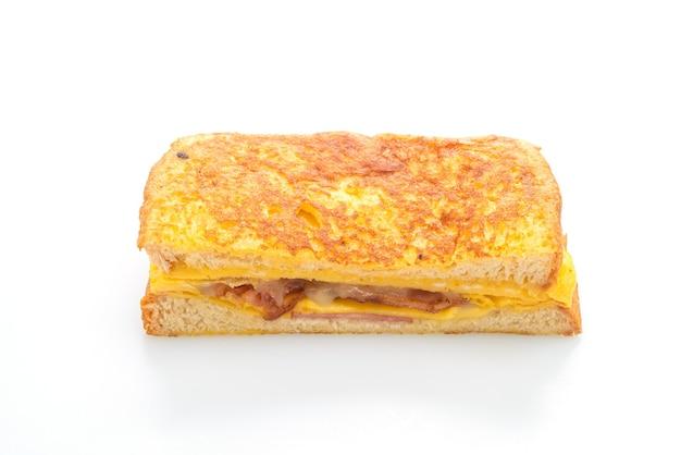 Francuska kanapka z szynką tostową z bekonem i serem na białym tle