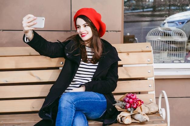Francuska kobieta w czerwonym berecie na ulicznej ławce