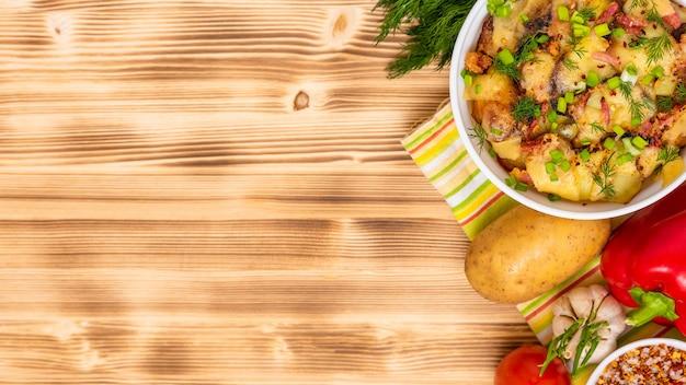 Francuska tartiflette z serem reblochon i ziołami na drewnianym stole. skopiuj miejsce. widok z góry.