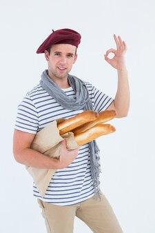 Francuski facet z beret mienia baguettes na białym tle