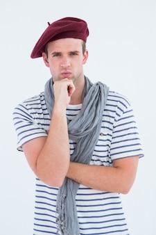 Francuski facet z beretem patrzeje kamerę