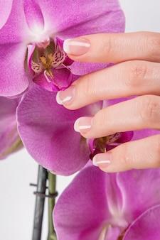 Francuski manicure i kwiat orchidei