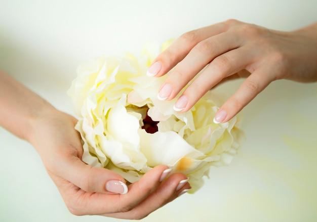 Francuski manicure paznokcie i biały kwiat piwonii na dłoni piękne kobiece dłonie spoczywające na białym over
