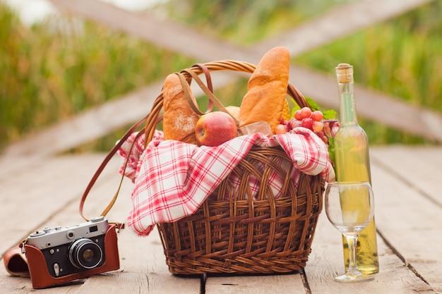 Francuski piknik prowincjonalny. kosz piknikowy w stylu retro z jedzeniem, aparat retro, butelka wina na drewnianym molo nad jeziorem