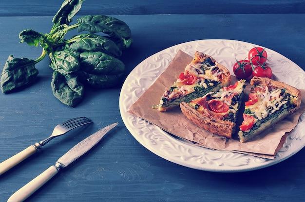 Francuski quiche z jajkami, świeżym szpinakiem, pomidorami i boczkiem