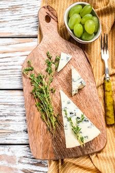 Francuski ser gorgonzola z winogronami. białe tło drewniane. widok z góry.