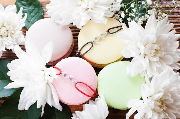 Francuskie ciasteczka makaronikowe z bransoletkami najlepszego przyjaciela. ładne dodatki z wisiorkami ze znakiem nieskończoności prezentowane na kolorowych cukierkach w kwiatowej ramce, zbliżenie