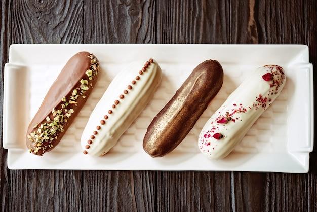 Francuskie deserowe eklery lub profiteroles z polewą czekoladową, z różnymi dodatkami na białym talerzu, drewniane tło. ciasto kremowe z kremem. miękka selektywna ostrość.