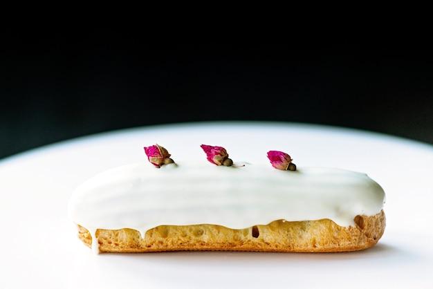 Francuskie deserowe eklery lub profiteroles z polewą z białej czekolady o smaku różanym, na białym tle. ciasta z kremem budyniowym, kremem różanym i posypką. miękka selektywna ostrość.