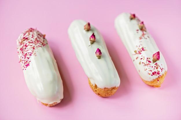 Francuskie deserowe eklery lub profiteroles z polewą z białej czekolady o smaku różanym, na różowym tle. ciasta z kremem budyniowym, kremem różanym i posypką. miękka selektywna ostrość.