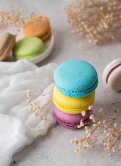 Francuskie deserowe kolorowe makaroniki na stole, ozdobione kwiatami i obrusem