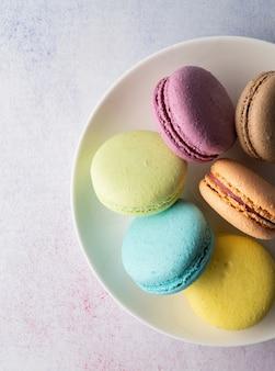 Francuskie deserowe kolorowe makaroniki na talerzu, minimalna koncepcja płaskiego lay