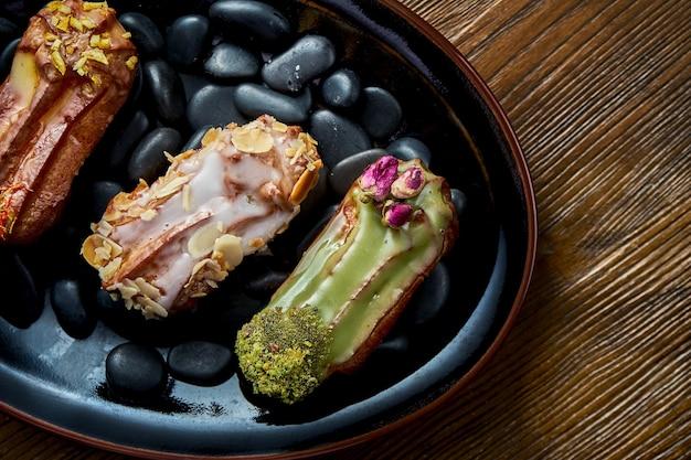 Francuskie eklerki z kremem i różnymi dodatkami podawane na czarnym talerzu na drewnianym tle. jedzenie w restauracji.