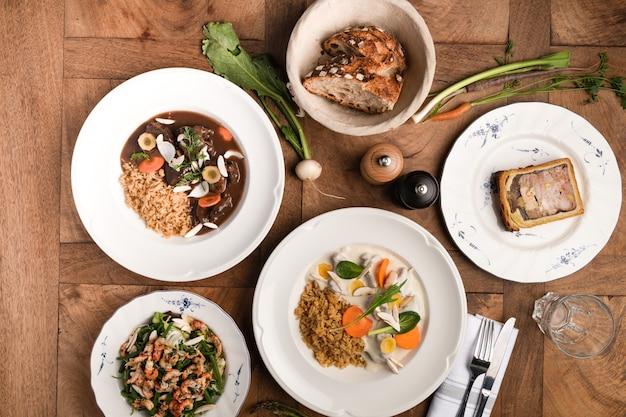 Francuskie i smakowe jedzenie w talerzach na drewnianym i tradycyjnym stole